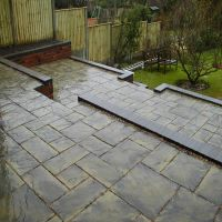 Reclaimed blue bricks used to edge a beautiful and practical patio laid by Country Lane Landscapes