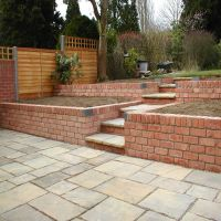 A beautiful garden with patio, steps, decorative wall and flower beds designed and landscaped by Country Lane Landscapes