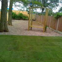 A lush new lawn with a luxurious garden seat on a spacious gravelled area by Country Lane Landscapes